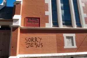 "The brick wall of St Gerrard's Catholic Church in Hawker Street, with graffiti saying ""SORRY JESUS"""