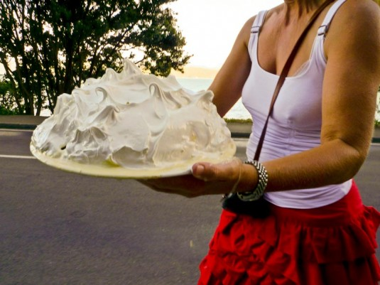 A woman in Karaka Bay carrying a mountainous pavlova across the road.