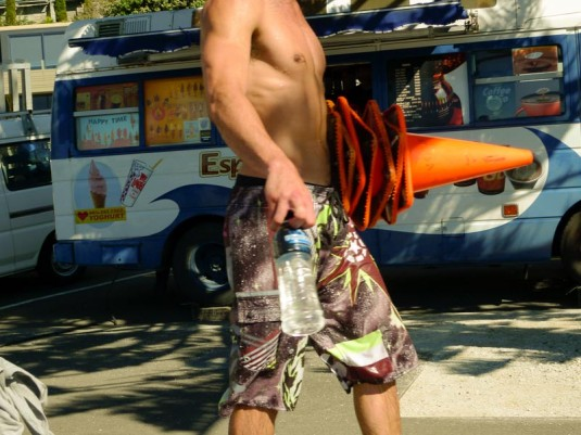 A headless shot of a topless man in boardshorts holding bottled water and 6 traffic cones in Oriental Bay.