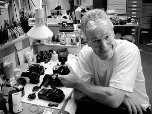 Black & white photo of Phil Jacobs at his workshop desk, which is covered in cameras in various states of disassembly.