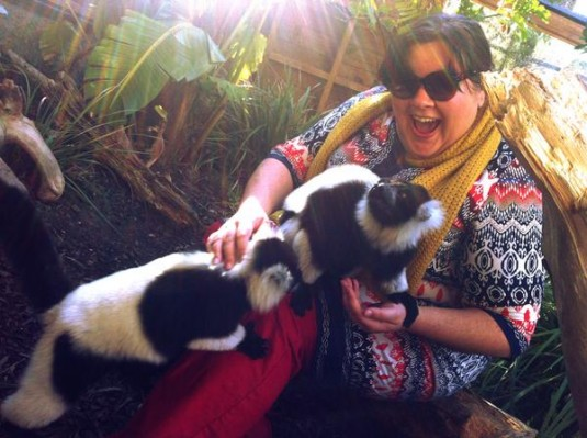 A fat girl is insanely overjoyed at the two fluffy creatures climbing on her lap