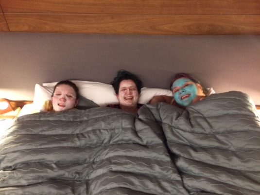 image of three people lying in bed wearing face masks