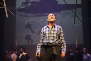 An older man stands centre stage. Behind him is a backdrop of soldiers rappelling from a helicopter.