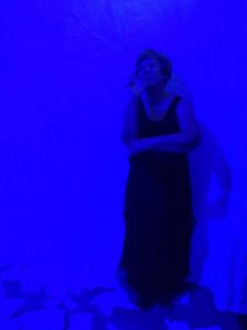 woman in a long black dress leans against a wall thoughtfully. she is lit by a blue light.