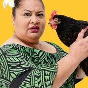Woman holding a a black chicken. They both look towards the camera.