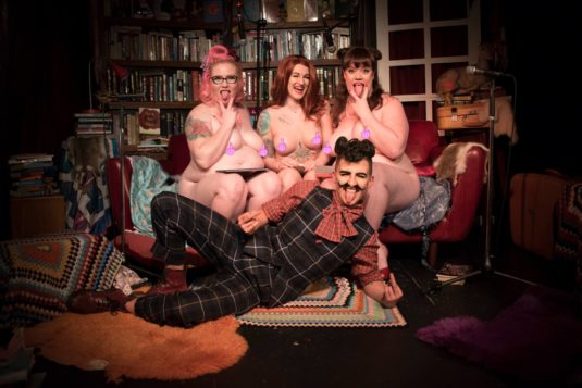three naked women and a drag king, nipples covered with emoji