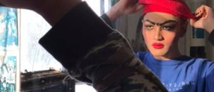 A person in a blue top adjusts a red beret on their head