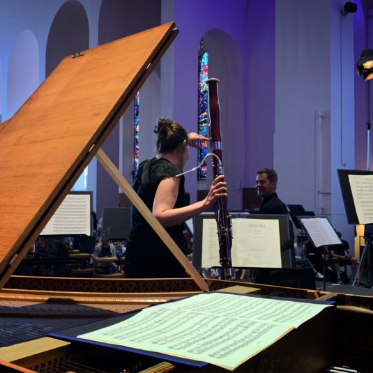Behind a harpsichord, a bassoonist talks to a colleague, with Händel scores on music stands.