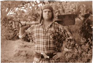 Sepia coloured photo of Geenty in a checkshirt, hat with ear flaps and a spade across his shoulders
