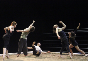 Four dancers are standing while one is on the ground between