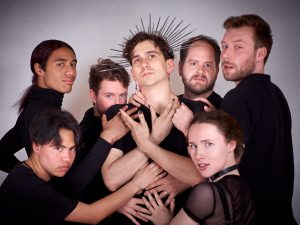 The cast of The Slutcracker surround Jake Brown who is wearing a star-like crown and posing with hands crossed in front of him. They are all looking out at the viewer.