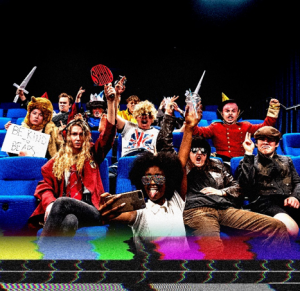 Promotional image of the cast rioting in their theatre seats